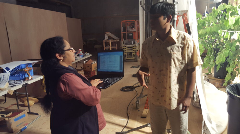 The Tamil coach stands with a laptop in hand together with an actor