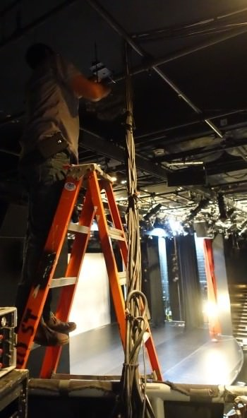 installer on a ladder with the stage as background<
